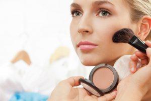 Using blush brush to apply blush on cheeks - professional makeup artist working
